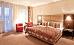 Doppelzimmer-Wohnbeispiel mit Doppelbett und Sitzecke
