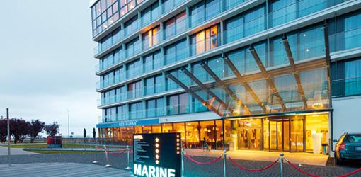 Beleuchteter Eingangsbereich des Hotels Marine während der Abenddämmerung